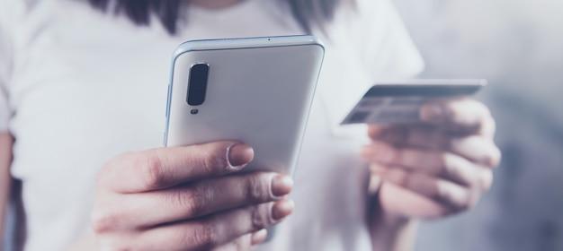 Menina segurando um telefone e um cartão do banco nas mãos