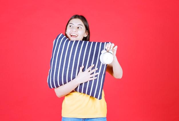 Menina segurando um travesseiro azul com listras brancas e mostrando um despertador.