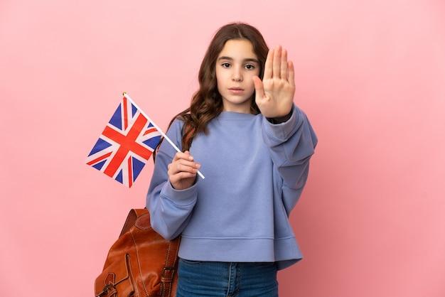 Menina segurando uma bandeira do reino unido isolada em um fundo rosa, fazendo um gesto de pare