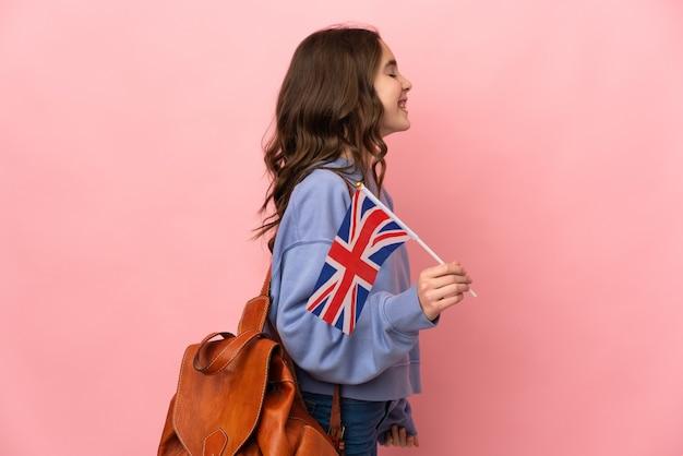 Menina segurando uma bandeira do reino unido isolada em um fundo rosa rindo em posição lateral