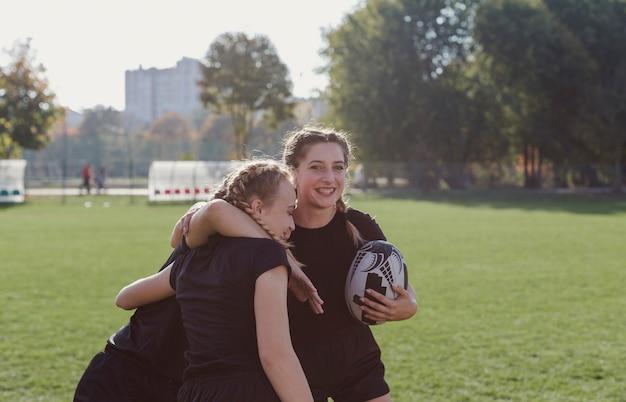 Menina, segurando uma bola de futebol e abraçando seus companheiros de equipe