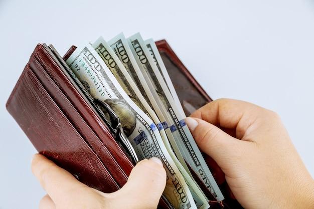 Menina segurando uma bolsa com notas de cem dólares em um fundo cinza. a garota tira uma nota de cem dólares da carteira.