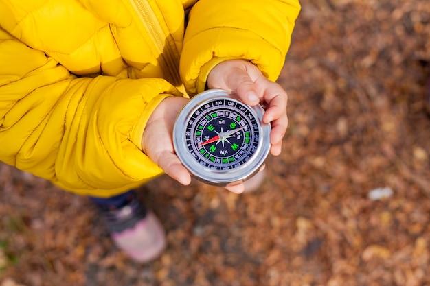 Menina segurando uma bússola na floresta