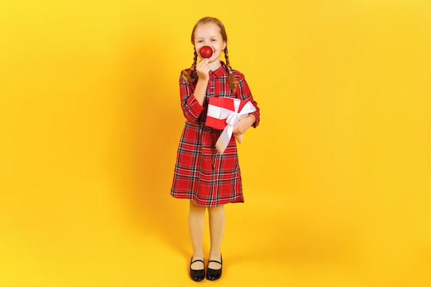 Menina, segurando uma caixa com um presente e fazendo o nariz de uma bola de natal.