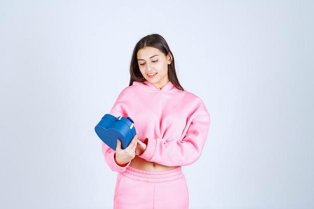 Menina segurando uma caixa de presente azul e olhando para ela.