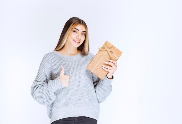 Menina segurando uma caixa de presente de papelão e aparecendo o polegar.