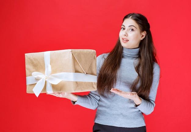 Menina segurando uma caixa de presente de papelão e apontando para ela.