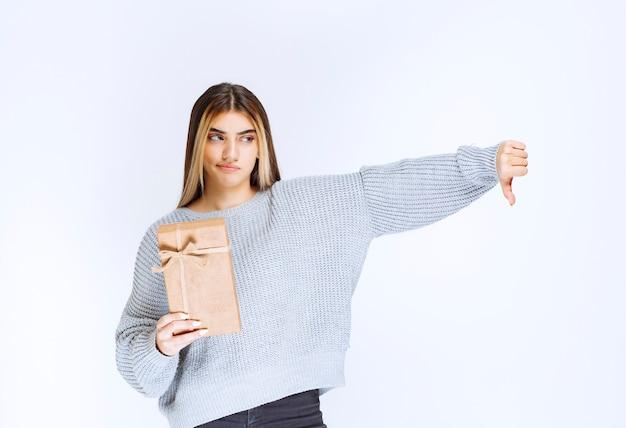 Menina segurando uma caixa de presente de papelão e mostrando o polegar para baixo.