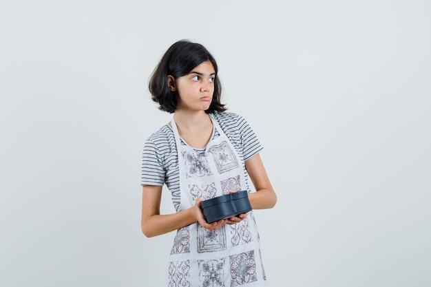 Menina segurando uma caixa de presente em uma camiseta, avental e parecendo hesitante,