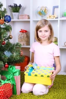 Menina segurando uma caixa de presente perto da árvore de natal na sala