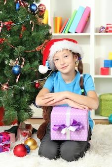 Menina segurando uma caixa de presente perto da árvore de natal