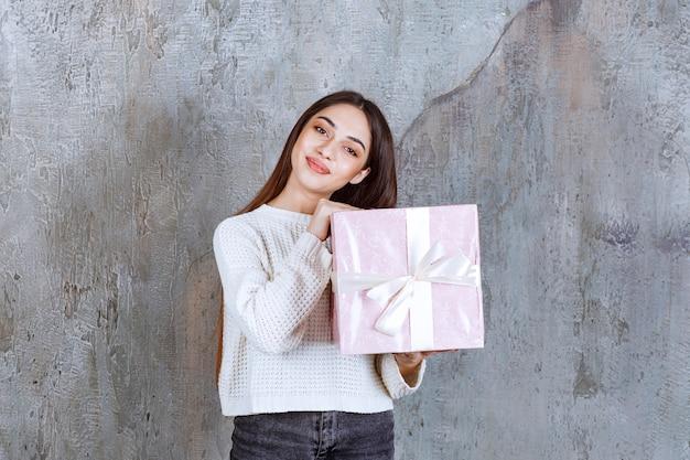 Menina segurando uma caixa de presente roxa embrulhada com fita branca.