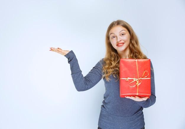 Menina segurando uma caixa de presente vermelha e apontando para alguém à esquerda.