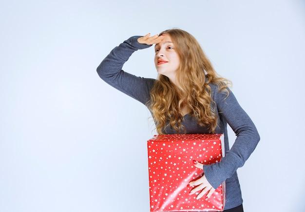 Menina segurando uma caixa de presente vermelha e procurando por alguém.