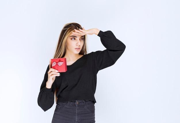 Menina segurando uma caixa de presente vermelha e vendo alguém vir recebê-la. foto de alta qualidade
