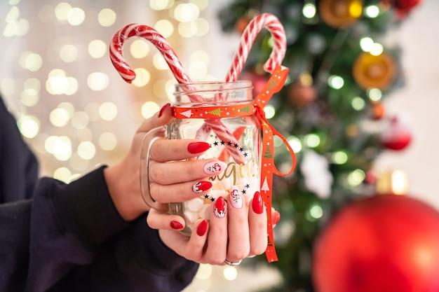 Menina segurando uma caneca cheia de doce cana de natal. manicure nas mãos no estilo de ano novo.