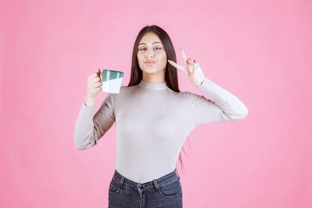 Menina segurando uma caneca de café e enviando mensagem de paz