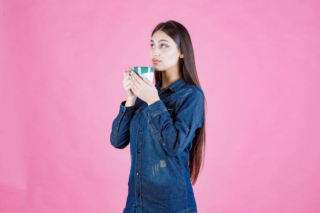 Menina segurando uma caneca de café verde branca e cheirando