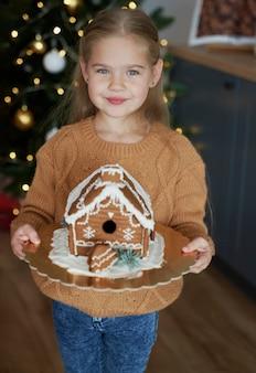Menina segurando uma casa de pão de mel decorada
