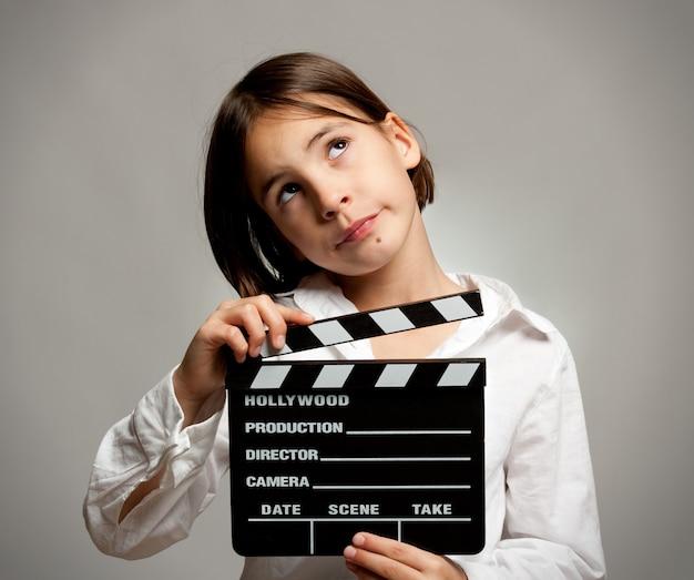 Menina, segurando uma claquete de cinema em um fundo cinza