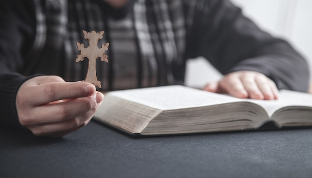Menina segurando uma cruz cristã e orando sobre a bíblia