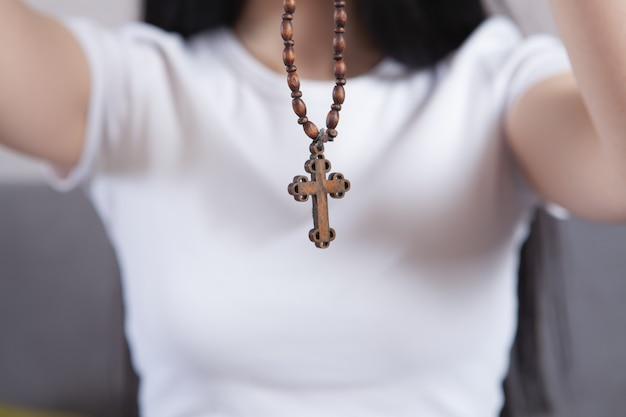 Menina segurando uma cruz de madeira