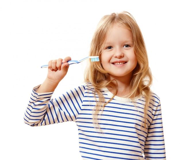 Menina segurando uma escova de dentes.