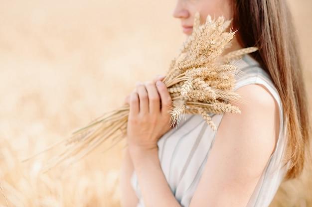 Menina segurando uma espiga dourada de trigo em um campo de trigo. mulher segura trigo com as duas mãos.
