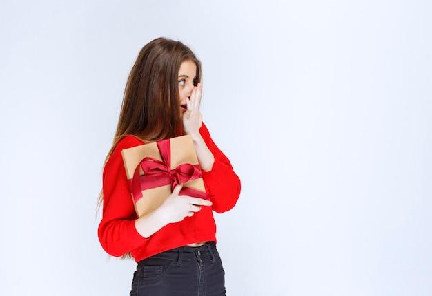 Menina segurando uma fita vermelha embrulhada em caixa de papelão e parece estressada e apavorada.