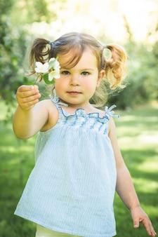 Menina segurando uma flor ao ar livre