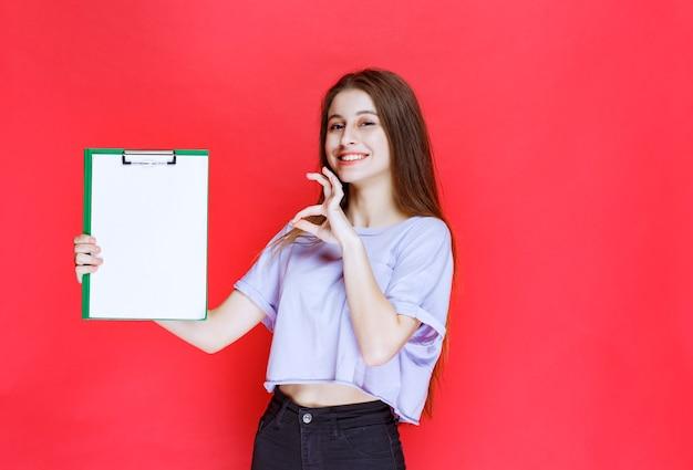Menina segurando uma folha de relatório em branco e mostrando sinal de prazer.