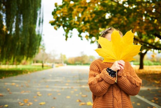 Menina segurando uma grande folha outonal na frente do rosto