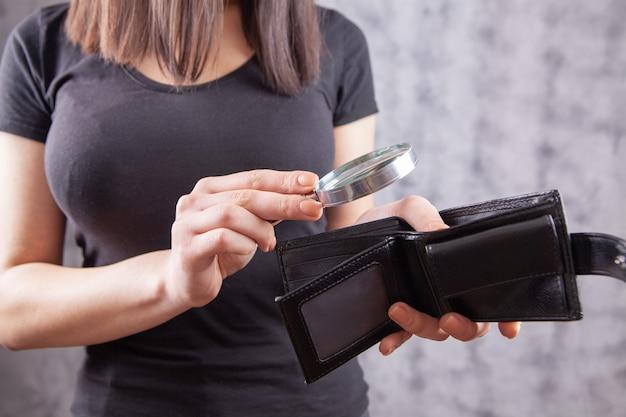 Menina segurando uma lupa e uma carteira