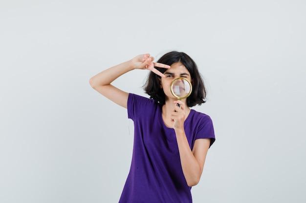Menina segurando uma lupa, mostrando o sinal v na camiseta,