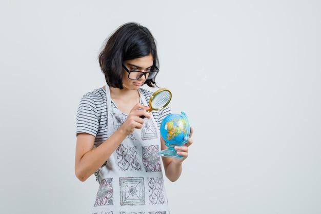 Menina segurando uma lupa sobre o globo da escola em uma camiseta, avental,