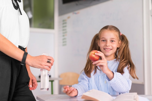 Menina segurando uma maçã ao lado da professora