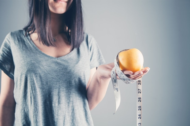 Menina segurando uma maçã e uma fita métrica. dieta e conceito de comida saudável em cinza