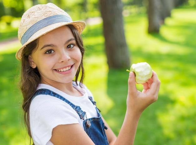 Menina segurando uma maçã enquanto olha para a câmera