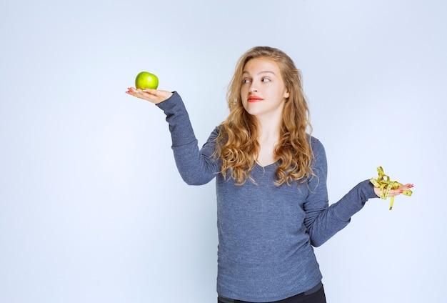 Menina segurando uma maçã verde em uma mão e uma fita métrica na outra.