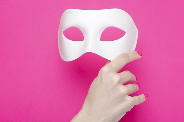 Menina segurando uma máscara de carnaval branca e uma pena macia sobre fundo rosa fúcsia