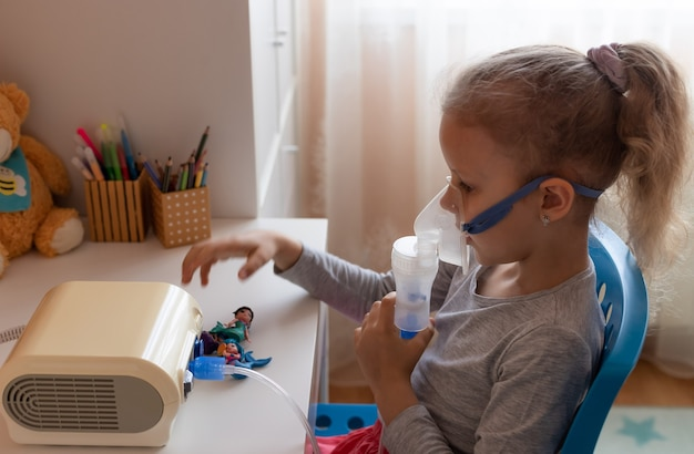 Menina segurando uma máscara inalatória sentada à mesa temporada de gripe