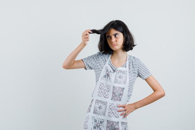 Menina segurando uma mecha de cabelo em uma camiseta, avental e parecendo pensativa,