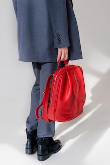 Menina segurando uma mochila de couro vermelho na mão