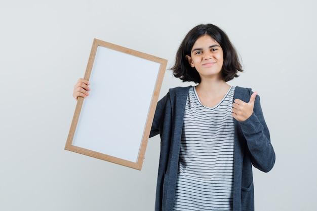 Menina segurando uma moldura vazia, aparecendo o polegar em t-shirt, jaqueta e olhando alegre.