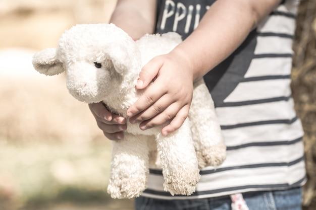 Menina, segurando uma ovelha de brinquedo