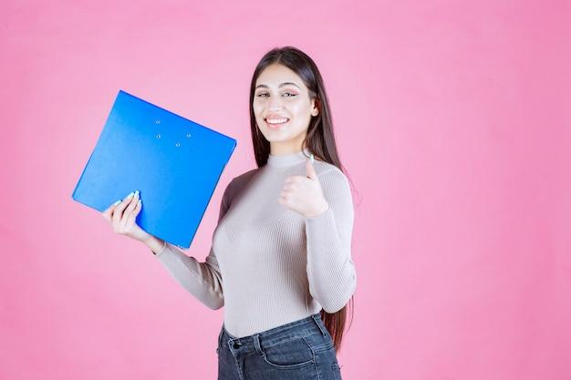 Menina segurando uma pasta de projeto azul e parece bem-sucedida e feliz