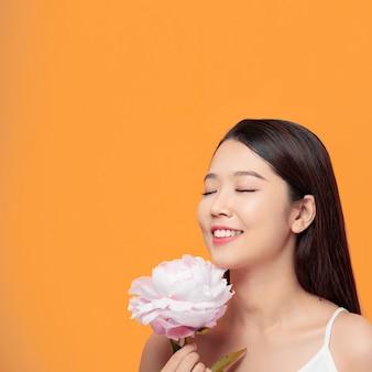 Menina segurando uma peônia de flor com roupas brancas
