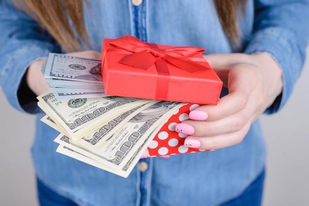 Menina segurando uma pilha de dinheiro na caixa de presente