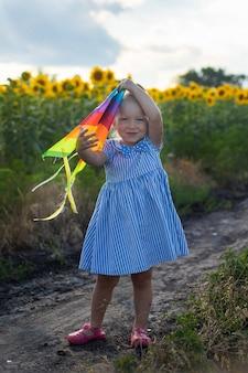 Menina segurando uma pipa em um campo de girassol.