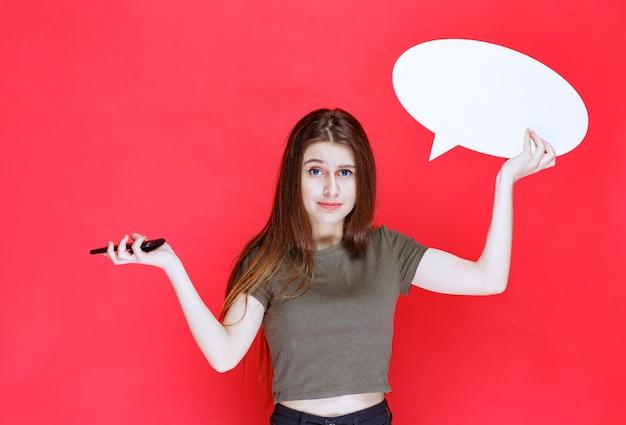 Menina segurando uma placa de informações ovale em branco e falando ao telefone.